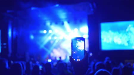прожектор : rock concert, fans audience shoot on mobile phone performing of musical group on brightly illumination Стоковые видеозаписи
