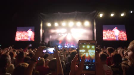película de filme : KHERSON, UKRAINE - JULY 13, 2019: crowd admirers make photos and videos on mobile phone on live music rock concert against bright lit stage with large screens at night In dark