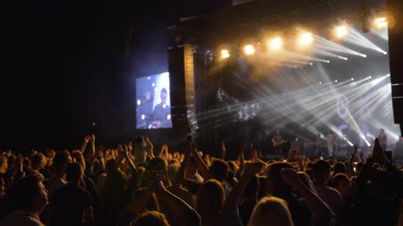 concert crowd : KHERSON, UKRAINE - JULY 13, 2019: crowd fans clap hands at rock live music party against brightly lit scene with large screens at night Stock Footage