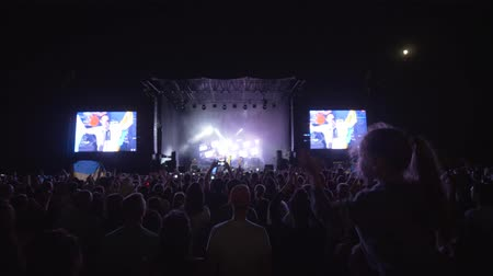 прожектор : KHERSON, UKRAINE - JULY 13, 2019: crowd people jump and clap hands at rock live music concert against brightly lit stage with large screens at night