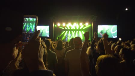 прожектор : KHERSON, UKRAINE - JULY 13, 2019: fan with mobile phone in hands makes video of live rock concert among crowd against brightly lit scene with spotlights at night Стоковые видеозаписи