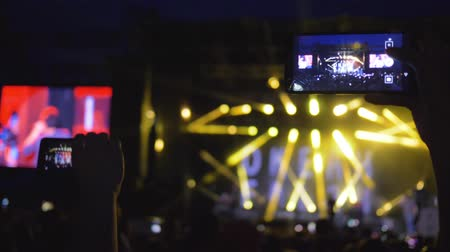 searchlight : KHERSON, UKRAINE - JULY 13, 2019: fans with mobile phones into hands delight live music at rock concert in bright scene lights in evening