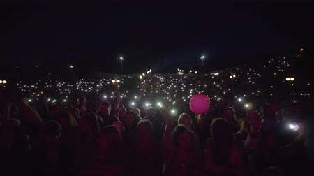 floodlight : KHERSON, UKRAINE - JULY 13, 2019: lot people fans with flashlights on mobile phone waving hands and enjoy musical art during night outdoor concert on open air