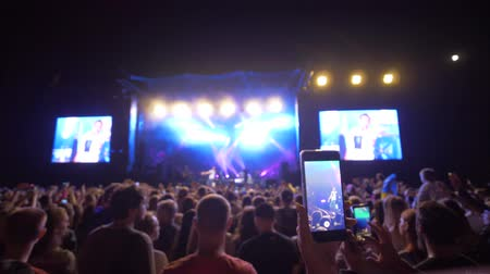 прожектор : KHERSON, UKRAINE - JULY 13, 2019: musical art, mobile phones in hands of admirer shoot video of rock concert on brightly lit stage