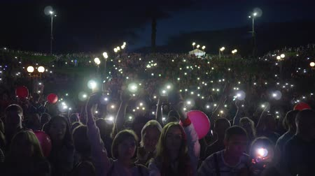 прожектор : KHERSON, UKRAINE - JULY 13, 2019: outdoor festival, crowd fans with flashlights on smartphone waving hands and enjoy live music during night concert on open air