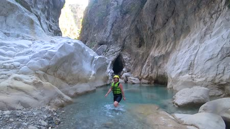 fejest ugrik : extremal excursion, active summer weekends of happy girl tourist in protective helmet and special clothes walk through mountain cave lets follow me into water