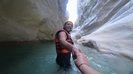 fejest ugrik : extreme honeymoon, young happy male tourist in protective clothes holding hand and leading his wife along water in cave among the stones