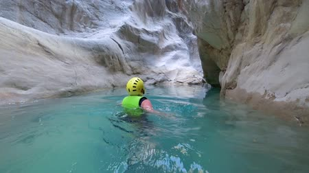 entusiasmo : extreme travel, active lifestyle holiday of a woman in extreme conditions is swimming in protective clothing between huge stones