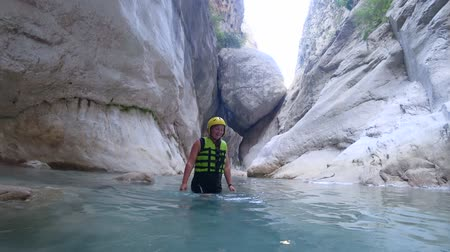 entusiasmo : extreme vacation, young happy tourist girl in protective clothing admires extreme tour in summer vacation is considering beautiful cave with sea dipping into water