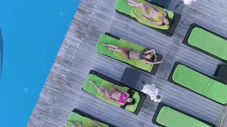 deck chairs : summer resort, attractive happy female friends into swimsuit relaxing on deck chair near blue pool in expensive resort during weekend, top view