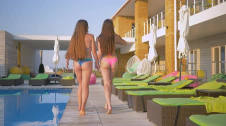 barefooted : beautiful long haired women friends into bathing suit have rest near swimming-pool during summer weekend at expensive resort Stock Footage