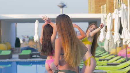 купальный костюм : cheerful company of attractive girls into bathing suit having fun near swimming-pool at expensive resort during summer weekend