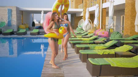 купаться : happy attractive girlfriends into bathing suit with Inflatable rings walk near blue pool during summer holiday at luxurious resort