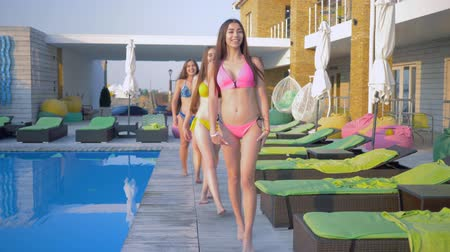 barefooted : Slender happy friends girls into swimsuit walk near blue poolside during summer vacation at luxurious resort Stock Footage