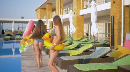 barefooted : summer fun, happy women friends into bathing suit with Inflatable rings have rest near blue pool during holiday at resort Stock Footage