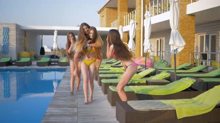 barefooted : happy friends on summer holiday, cheerful group of attractive long haired girls in swimsuits stroll by pool and lounger at resort