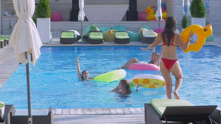 fejest ugrik : company of happy girls friends relaxes in swimming-pool and girlfriend with inflatable rings jumps beside to water with spray during vacation at luxurious resort