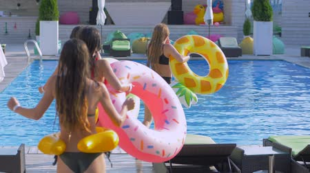 fejest ugrik : company of shapely cheerful girls in swimsuits with inflatable rings run and jump in pool at expensive resort while relaxing and lot of water splashes Stock mozgókép