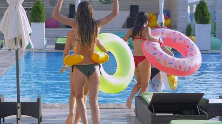 fejest ugrik : fun in swimming pool, company of slender cheerful girls into swimsuits with inflatable rings run in row and jump into blue poolside at expensive resort while holiday