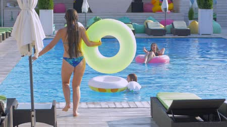 fejest ugrik : happy friends in summer pool, young women relaxes in poolside and girlfriend with inflatable rings jumps beside to water with spray during holidays at luxurious resort
