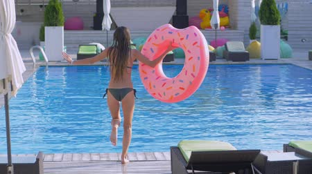fejest ugrik : slim girl with long wet hair in swimsuit with inflatable ring runs and jumps into pool at expensive summer vacation resort Stock mozgókép