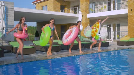 fejest ugrik : young attractive women friends in swimsuits with inflatable rings jump into blue water of swimming-pool while relaxing on expensive summer resort rest Stock mozgókép