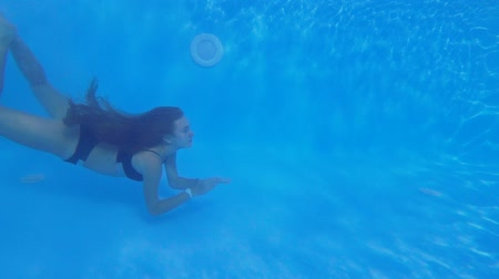 fejest ugrik : pool diving, long-haired young female into swimsuit floating underwater in clear blue poolside during summer holidays at resort, underwater shooting view Stock mozgókép