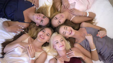 contestant : girls party, portrait of happy joyful beautiful girlfriends in pajamas lying on bed have fun chatting at a home party into room Stock Footage