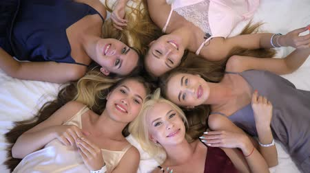 contestant : girls party, smiling girlfriends into sleepwear with beautiful make-up are lying on bed and having fun looking at camera at pajama party