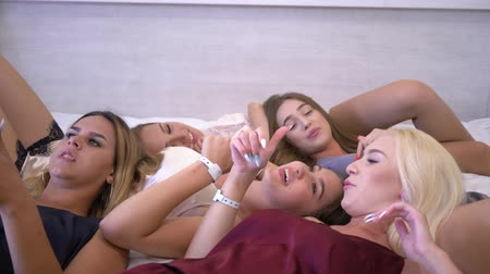 fiatalos : party at home, young emotional girls into sleepwear are actively gossiping communicating and lying together on bed gesticulating hands