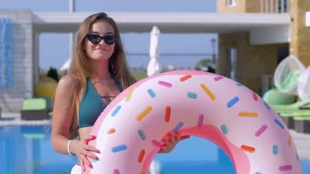 barefooted : beautiful glamorous girl into bathing suit and eyeglasses with inflatable rings flirts on camera near blue pool at expensive resort on summer vacation