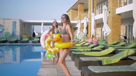 barefooted : happy company of cheerful girlfriends into bathing suits with inflatable rings walking and dancing near blue pool during summer holiday at luxurious resort Stock Footage