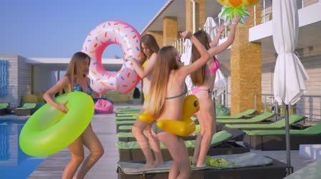 купальный костюм : pool party, company of beautiful girls into bathing suits dance sexually with rubber for swimming on sun lounger near swimming pool during summer holidays at luxury resort Стоковые видеозаписи