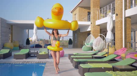 barefooted : summer holiday, happy beautiful young girl with perfect body and long hair near pool having fun playing with inflatable rings during vacation at a luxury resort