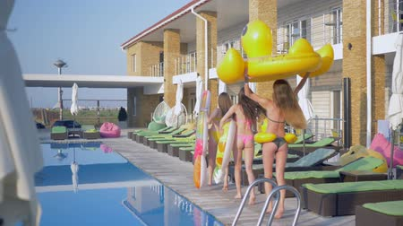 barefooted : summer holidays, young women with long hair and slender tanned bodies having fun at girls pool party into expensive resort Stock Footage