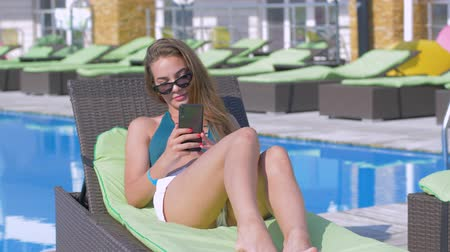 plážové lehátko : young attractive woman into bathing suit and sunglasses takes selfie photo on mobile phone during relaxing on lounger by pool at expensive resort during vacation