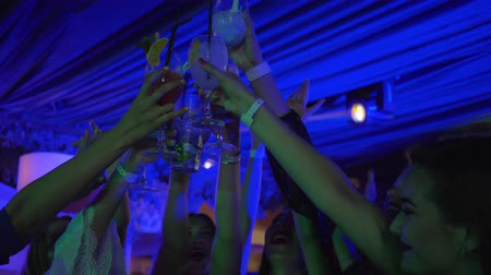 personalidade : cheerful girlfriends rejoicing together and drinking alcoholic cocktails at the nightclub party Stock Footage