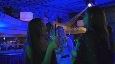 personalidade : girlfriends in a nightclub have fun chatting and drinking alcohol cocktails and dancing on the dance floor during a bachelor party Stock Footage