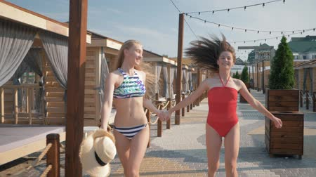 bounce : cheerful girlfriends with slim bodies in swimsuits run holding hands during summer vacation in a luxurious resort
