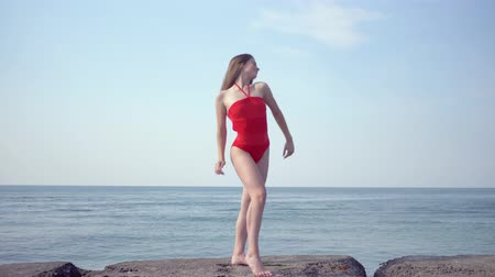 招待状 : beautiful slim girl in a swimsuit enjoys summer day and the suns rays on sea coast on happy weekend