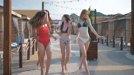 bungaló : happy girlfriends, young women with beautiful slender bodies in swimsuits running, having fun and laughing during sea holidays on the coast in a bungalow