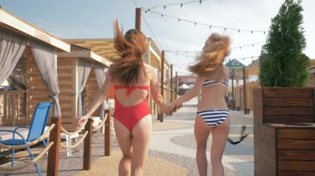 bounce : summer fun, happy slender young girls into swimsuits have fun running along seafront with bungalows against backdrop of luxury expensive hotel Stock Footage