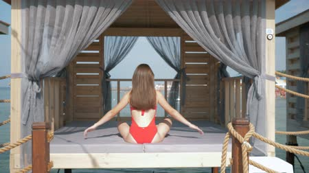 hívogató : sunny vacation, young woman in a swimsuit with a beautiful body relaxes in bungalow on the sea coast of an expensive resort in a lotus position, rear view