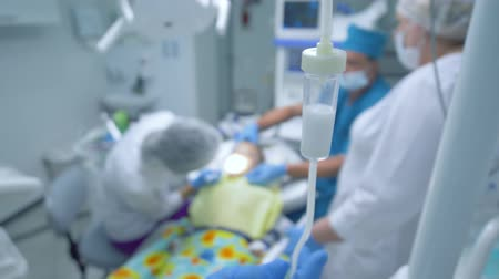 narcosis : care for patient during an operation under anesthesia on teeth, a doctor with gloves checks an intravenous dropper with a medicine, troubleshooting Stock Footage