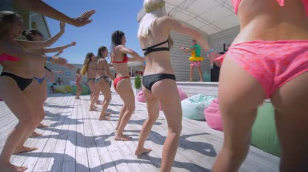 contestant : LAZURNOE, UKRAINE- JULY 13, 2019: active vacation, a group of beautiful girls in swimsuits at a luxury resort move to music with animators having fun