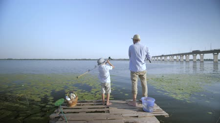снасти : family relationships, parent man and his happy son throw fishing rods in river fishing on a wooden pier against background of a bridge in suburbs during a weekend in nature