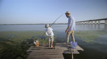 захват : catch a fish, little boy fishing on pier near river with his happy father against blue sky during summer holidays