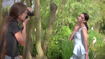 professional photography : KHERSON, UKRAINE- JULY 04, 2019: professional woman photographer takes pictures of luxury fashion model in designer clothes photo shoot in a beautiful green park