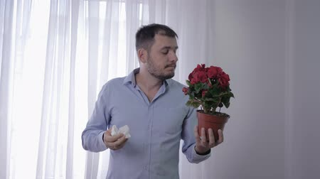 zsebkendő : allergies men, male with flower in his hands suffers from respiratory disease sneezes and wipes his face due to sensitivity to pollen Stock mozgókép