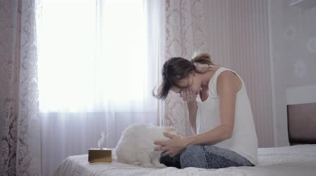 zsebkendő : allergy to fur, beautiful female plays with cat on bed and suffers from pathogen of respiratory disease sneezes and wipes her face with napkins